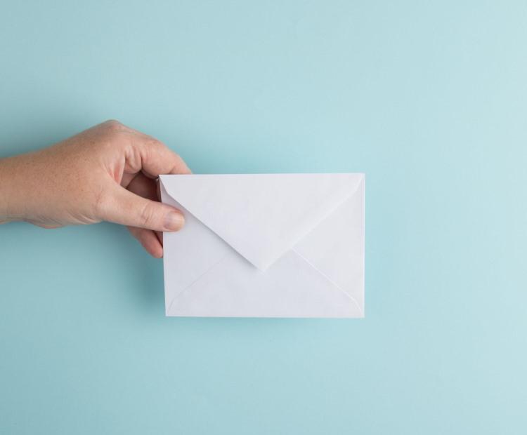 Hånd som holder en hvit konvolutt