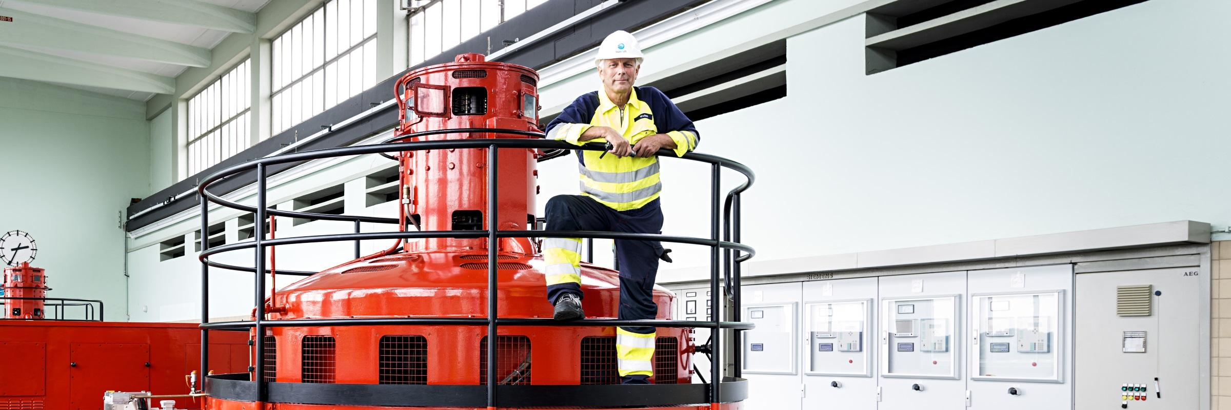 Mann står i maskinhallen på et vannkraftverk