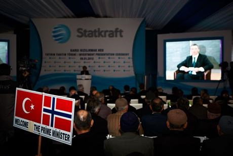 board with norwegian and turkish flag in front of big screen with man