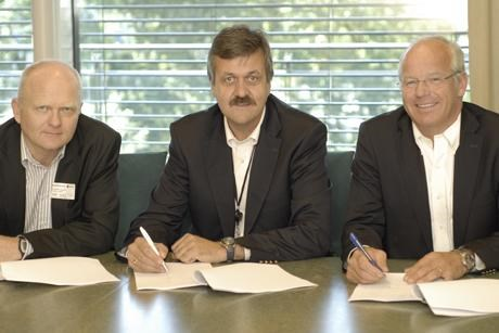 Three men signing contracts