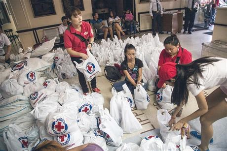 Volunteers from Red Cross packs bags.