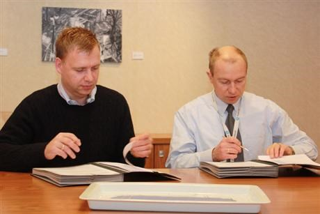 Two men sitting at table signing contract